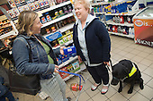 Visually impaired woman in a shop with a guide dog. MR