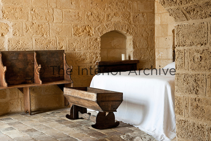 An old wooden cot standing at the feet of the bed in one of the bedroom at the unique Albergo Diffuso Le Grotte della Civita in Southern Italy housed in restored caves