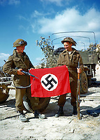 These two Canadian soldiers raise a Nazi flag which they captured in France,<br /> <br /> ca summer 1944<br /> Author <br /> <br /> credited to National Archives of Canada