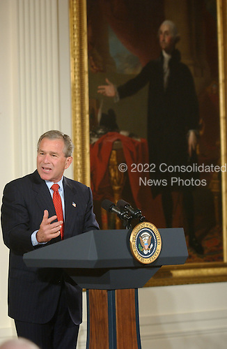 United States President George W. Bush makes remarks at the White House ceremony where the Clinton portraits were unveiled at the White House in Washington, D.C. on June 14, 2004.  The President is in front of the Gilbert Stewart portrait of President George Washington..Credit: Ron Sachs / CNP