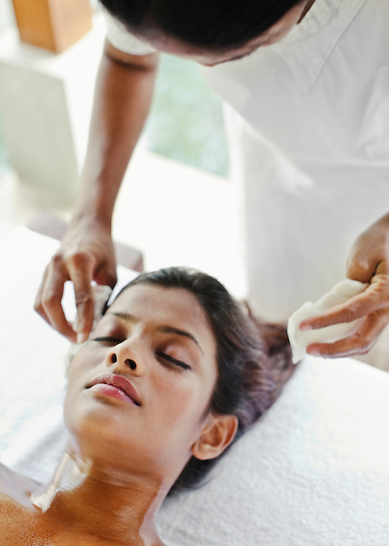 A young woman receives a Nourishing Pink Clay Facial treatment at Sahana Spa, Saman Villas, Aturuwella, Bentota, Sri Lanka. The Nourishing Pink Clay Facial is a 70-minute treatment that helps stimulate blood circulation in the face, while gently exfoliating and cleansing the skin. It was designed for dry and sensitive skin.