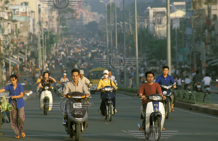 Motorcycles and scooters drive down a busy Saigon street.