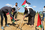 Palestinians hold their national flags as they plant olive trees to mark Land Day during a symbolic ceremony held in the village of Abassan, east of Khan Yunis near the border fence between Israel and the southern Gaza Strip on March 31, 2015. On the annual Land Day, demonstrations are held to remember six Arab Israeli protesters who were shot dead by Israeli police and troops during mass protests in 1976 against plans to confiscate Arab land in the Galilee. Photo by Abed Rahim Khatib