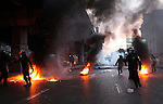 Police threw rocks and fired tear gas from behind burning tires in downtown Cairo, Egypt, Jan. 26, 2011. Violent clashes between demonstrators and police continued into a second day, as protesters attempted to build momentum in a movement inspired by the recent Tunisian uprising.