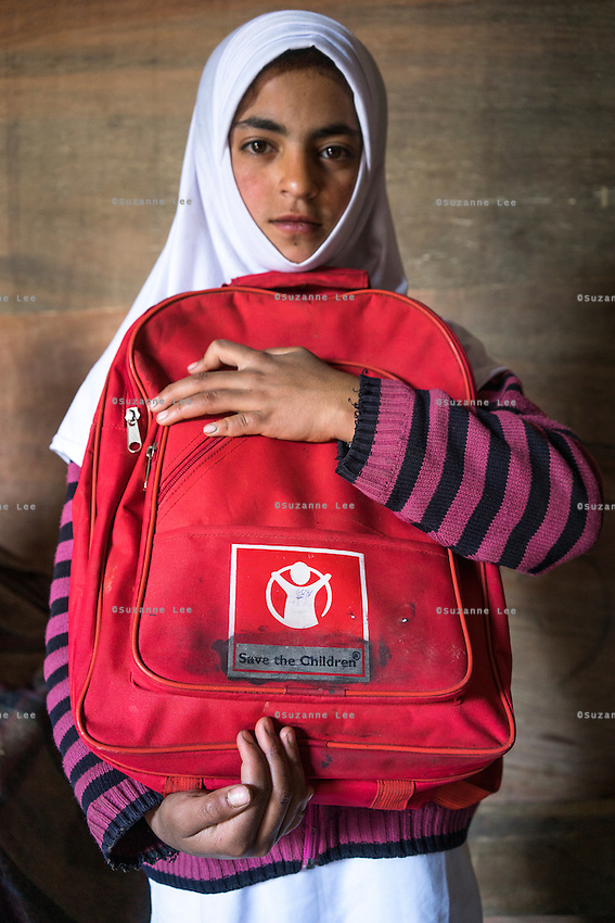 (Alison Griffin to fill in names) (Name) hugs her education kit inside her temporary shelter in Abikarpora village on the Dal Lake, Srinagar, Jammu and Kashmir, India, as seen here on 25th March 2015. Since the flood, her mother has been widowed, and is left with four young children and no home. Her family now lives in a temporary shelter built using the emergency shelter kit, and continues their recovery with the help of relief kits such as education kit, food basket, hygiene kit and non-food items from Save the Children. Photo by Suzanne Lee for Save the Children