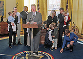 United States President Bill Clinton announces a proposed new rule that will allow the states to use their unemployment compensation systems to help offer paid leave to new parents in the Oval Office of the White House in Washington, DC on 30 November, 1999.  US Secretary of Labor Alexis Herman (at far right) picks up the pacifier of one of the younger participants in the photo op.<br /> Credit: Ron Sachs / CNP