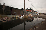 QUEENS, NY -- OCTOBER 19, 2013:  A pile of bricks, where Bansky later placed a shying sculpture, sits in a puddle on October 19, 2013 in Willets Point, Queens, NY.  Photographer: Michael Nagle for The New York Times