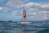 Fit, athletic woman standup paddles at Palauea Beach (aka White Rock) near Wailea, Maui.