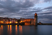 Eglise Notre Dame des Anges, Collioure, France, seen from the sea in the evening with the street lights reflected in the water. The bell tower was converted from a medieval lighthouse and the Mediterranean Gothic style nave was built in 1684. The dome was added to the bell tower in 1810. Picasso, Matisse, Derain, Dufy, Chagall, Marquet, and many others immortalized the small Catalan harbour in their works. Picture by Manuel Cohen.