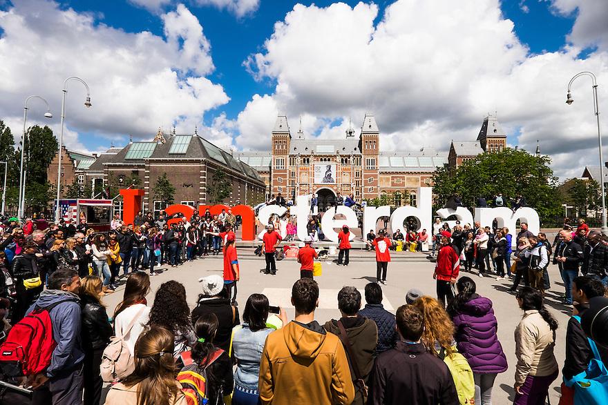 Nederland, Amsterdam, 30 mei 2015<br /> Performance van groep buitenlandse straatartiesten op het Museumplein, vlak voor het I amsterdamlogo en het Rijksmuseum.  Toeristen laten zich graag vermaken door dit soort artiesten, ze staan er in een grote kring om heen.<br />  <br /> Foto: Michiel Wijnbergh