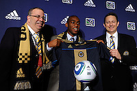The sixth overall pick Amobi Okugo (UCLA) of the Philadelphia Union with Philadelphia Union President Tom Veit (L) and CEO & Operating Partner Nick Sakiewicz (R) during the MLS SuperDraft at the Pennsylvania Convention Center in Philadelphia, PA, on January 14, 2010.
