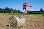Teenager Boy Jumping off Hay Bale