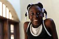 Young girl at an orphanage supported by EDV, Port-au-Prince, Haiti. EDV is committed to affecting permanent change in disaster-affected communities worldwide. Their role is to facilitate personal connections between volunteers and the survivors of disasters.  The charity is based on a proven model developed by several landmark organisations that have paved the way for citizens to become disaster volunteers. These landmark organisations have shown that supposedly ordinary people working together with the guidance of knowledgeable leaders can make an extraordinary difference in the lives of those affected by disaster..EDV believe that to provide meaningful relief and reconstruction assistance to disaster affected communities they have to do more than reconstruct buildings. They need to understand and address the factors that made a community vulnerable to the disaster in the first place. The charity's work is organised with these factors in mind so that they can affect change that far outlives their presence..EDV believes that survivor motivation is essential to the recovery of any disaster-affected community. Their operations will always be predicated on the idea that survivors may be traumatised, but they are not helpless. With this in mind, EDV encourages host communities to direct their own recovery. EDV believe that this empowerment is essential in helping survivors feel a renewed sense of control over their lives which will, in turn, help overcome the feelings of hopelessness that can follow a disaster and inhibit long term recovery. EDV also believe that social cohesion is of primary importance in any disaster-affected area. No amount of bricks or mortar will bring about sustainable improvement if communities fail to come together or are disrupted by relief efforts. Therefore, their operations will always aim to foster communication and cooperation within and between the communities they serve.
