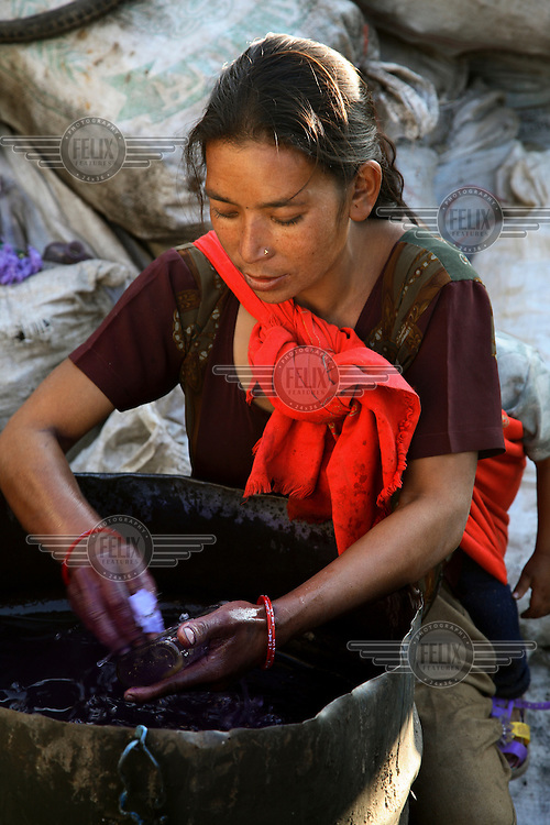 A young mother washes bottles at a glass recycling business.