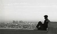 Young man looking at a view of downtown Los Angeles from the Griffith Park Observatory.