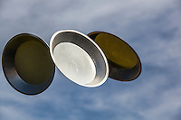 On Pi(e) Day, 3-14, pie pans float against a blue sky with high clouds.