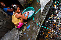 A Colombian girl washes clothes in a bucket, outside a wooden house in the stilt house area in Tumaco, Colombia, 14 June 2010. Although Latin America (as a whole) is blessed with an abundance of fresh water, having 20% of global water resources in the the Amazon Basin and the highest annual rainfall of any region in the world, an estimated 50-70 million Latin Americans (one-tenth of the continent's population) lack access to safe water and 100 million people have no access to any safe sanitation. Complicated geographical conditions (mainly on the Pacific coast), unregulated industrialization (causing environmental pollution) and massive urban poverty, combined with deep social inequality, have caused a severe water supply shortage in many Latin American regions.