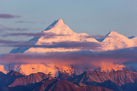 Pink sunset light falls on the snowy summit of Mt Brooks of the Alaska range mountains in Denali National Park, interior, Alaska.