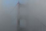 Dense morning fog dances around the north tower of the Golden Gate Bridge as seen from Fort Baker, San Francisco, California.