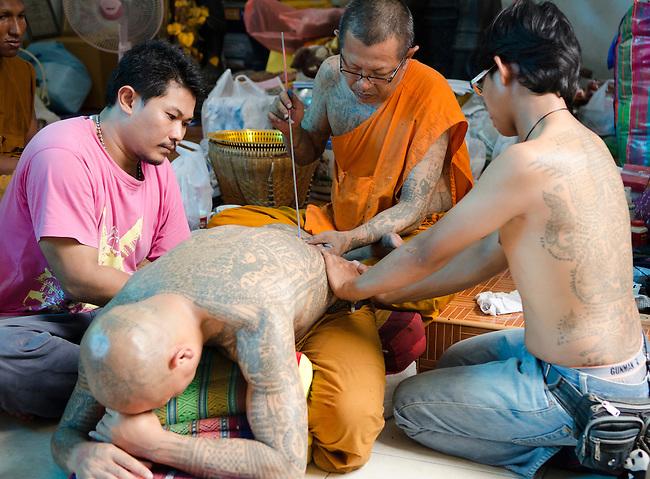 Nakorn Chai Sri, Thailand, March 2, 2012, Wat Bang Phra Buddhist Monk gives a devotee a sak yant magical tattoo.
