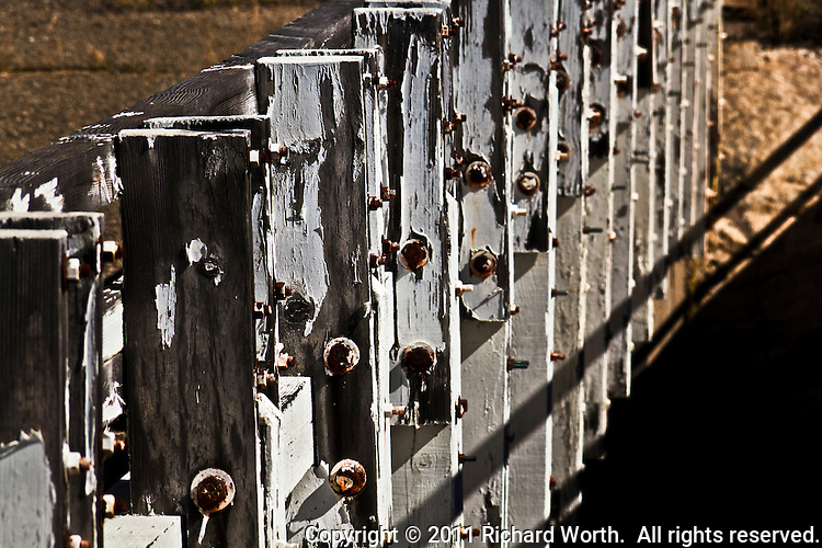 Peeling white paint and the raised grain of old wood - vertical siderailing held in place by rust-red nuts and bolts.  Preserved remnants of the Dardanelles Bridge, circa 1933, along the Middle Fork Stanislaus River, Sierra Nevada Mountains.