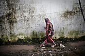 An old woman is seen taking a careful step as she walks over mud at the transit camp in Badagabapur, in Jagatsinghpur, Orissa. Posco Transit Camp is being set up for people who have been driven out of their villages for being pro-Posco, where they live on the side of a highway on $80 a day shared between 195 people.