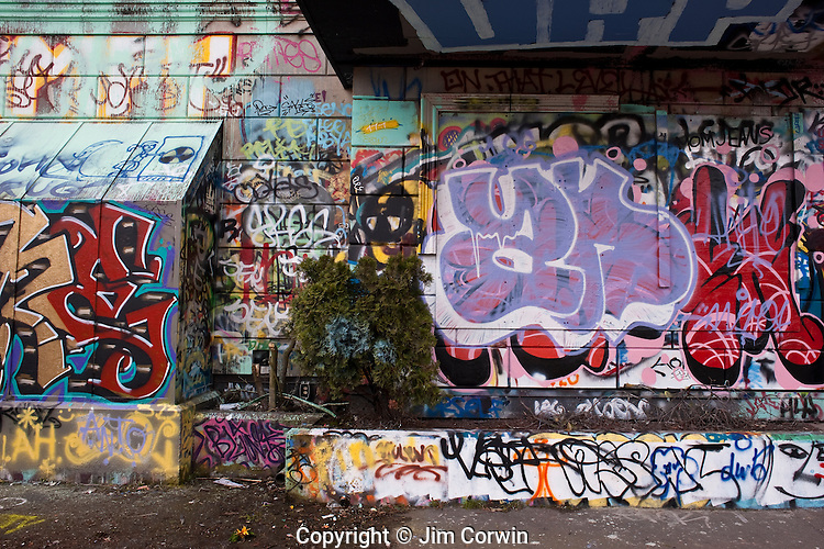 Street scene where a building is covered with graffiti, drawings, words, phrases