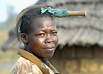 A woman in a camp for internally displaced persons in northern Uganda rests her scythe on her head. The two-decade conflict began winding down with peace talks in 2006, and some displaced families have returned home.