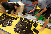 Painting banners on board the Greenpeace ship Rainbow Warrior, as it transits northwards to Fukushima, Japan, on Monday 25th April 2011.