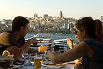 Diners enjoy a meal on the Hamdi restaurant balcony overlooking the Golden Horn and Galata  Tower in Istanbul, Turkey.