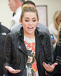 "Miley Cyrus speaks to volunteers at the Sharing the Spirit Holiday Party held for Orange County's shelter and motel kids at South Coast Plaza on Friday night. ""I don't just stop at one thing that's important to me,"" she told the kids in urging them to keep volunteering to help others in their communities. ""Whatever makes you happy, that's what you give."""
