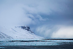 Alkefjellet, a large bird colony in Arctic Svalbard, Norway.  A snowstorm in the distance creates a dramatic arctic sky.