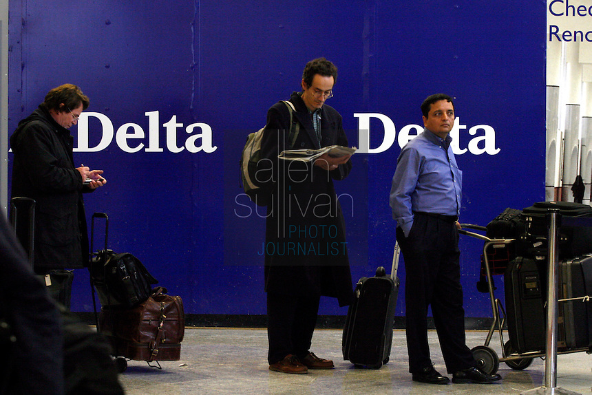 Passengers wait in line at a Delta Air Lines check-in counter at Hartsfield-Jackson Atlanta International Airport. US Airways has made a bid to take over Delta Air Lines, which is headquartered in Atlanta.<br />