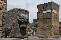 Fountain, corner of Via Di Nola, Pompeii, with an animal's head carved on a block of stone. One of 42 public fountains fed by lead piping from water towers around the city