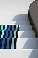 A broad striped cotton with a black background and designed by Sonia Rykiel for Lelievre graces the whitewashed steps of the villa
