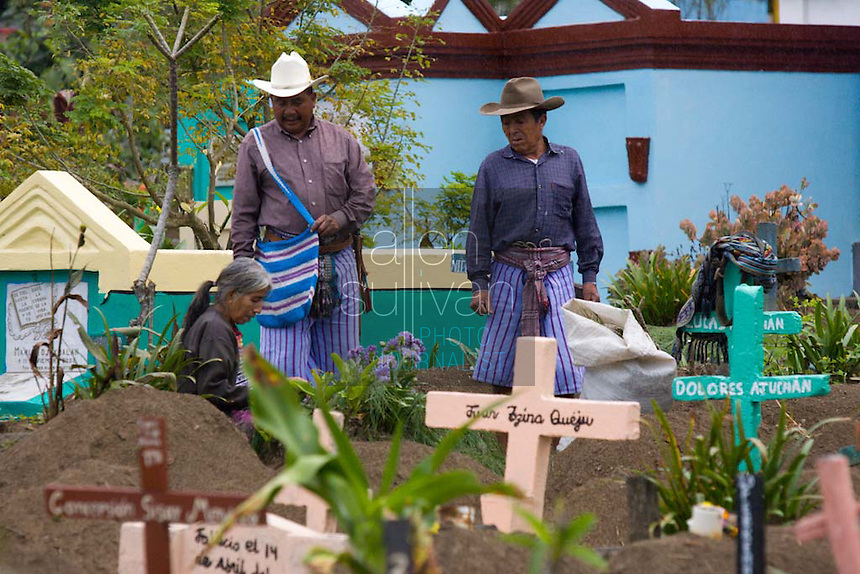 People decorate the gravesites of loved ones during Day of the Dead memorial celebrations in the cemetery of Santiago Atitlán, Guatemala. Early in October, a mudslide practically destroyed the nearby Mayan town of Panabaj, killing scores of people and leaving many others homeless.