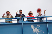"People on a bridge wave at the passing ""Berlin Beats and Boats"", a techno party on a series of boats that cruise down the River Spree through Berlin and the surrounding countryside, replacing the now defunct ""Love Parade"".."