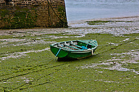 With the tide out, an Irish boat sits without water.