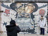 Tourists at the East Side Gallery, a portion of the former Berlin Wall that has been kept standing as a monument to freedom, take a picture in front of Leonid Brezhnev and Erich Honecker kissing.