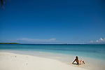 A woman sits on the sand looking at the turquoise water on Isla Pelikano, San Blas Islands, Kuna Yala, Panama