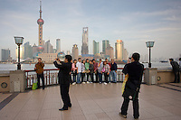 Tour group at the Bund pose for photographs in front of the Pudong financial and business district, Shanghai, China