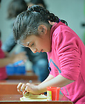 """A girl plays with modeling clay in a church-sponsored """"child-friendly space"""" in the village of Bakhtme, Iraq, which was flooded with displaced families when the Islamic State group took over nearby portions of the Nineveh Plains in 2014. The space is sponsored by the Christian Aid Program Nohadra - Iraq (CAPNI). It includes some children from the host community as well."""