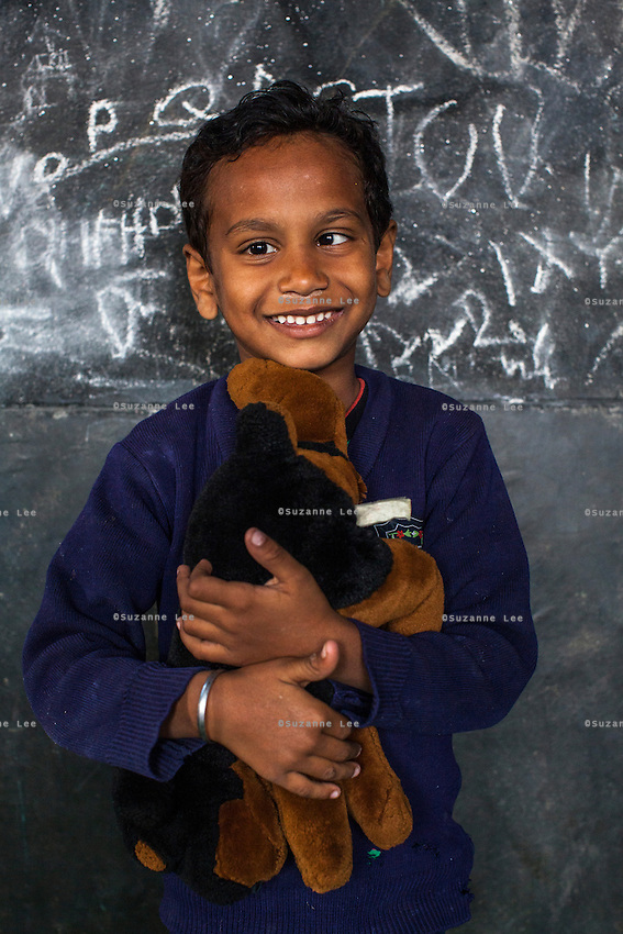 Saify, 5, poses for a portrait with a soft toy in the Guria Non-Formal Education center in the middle of the Shivdaspur red light district, Varanasi, Uttar Pradesh, India on 20 November 2013. Guria uses the soft toys as a form of therapy for the children of the women in prostitution and also use it as signals of the children's emotional wellbeing.