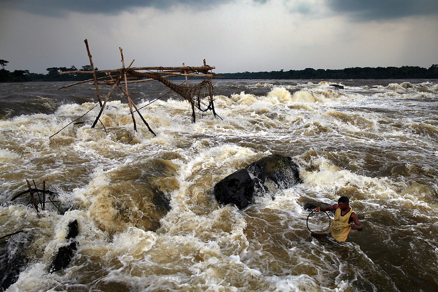 A fisherman uses a small net in the middle of the Congo river, at Kisangani, DR Congo. As well as the traditional bamboo nets the fishermen also use string and cast nets in the rapids to maximise the number of fish they can catch.