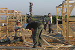 Under an Israeli military watchtower, settlers build wooden shacks at the Israeli outpost of Kerem Atzmona, in the Israeli settlement bloc of Gush Katif, Gaza Strip.<br />