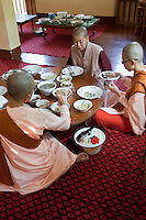 Myanmar, Burma.  Zayar Thein Gyi Nunnery, near Mandalay.  Buddhist Nuns Having Lunch, Sitting on the Floor.  Buddhist Monks and Nuns shave their heads while in service.