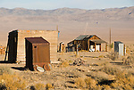 Two corrugated and one wooden outhouse, cabin and road to the mountains to the distant, Nevada