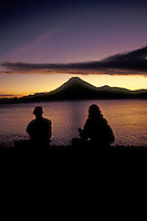 Young tourists, watchong the sun set over Lake Atitlan, Guatemala, at dusk