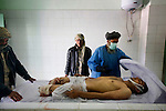 Imam Gul, left, 25, and Amanadin, center, 20, watch while a white shroud is pulled over the body of Hamidullah, 22, at the Mirwais Hospital morgue in Kandahar, Afghanistan, April 23, 2009. The day before, Ahmad Shei, 25, and Hamidullah, 22, were in an unarmored truck carrying material to a checkpoint in Zabul Province when their vehicle was hit by a roadside bomb. Four other border policemen were injured and taken to Kandahar Air Field to receive medical treatment. The two dead were to the morgue at Mirwais Hosptal before being transported to their home provinces in the North for burial. Despite worsening security, development continues at Mirwais Hosptial, where the International Committe of the Red Cross conducts training and assists the local staff. Mirwais is the main public hosptial serving five southern provinces. As security has deteriorated in the South, many international NGO's have pulled their staff from the area or shut down the regional office, stunting development in a region where it is badly needed.