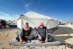 Two men and a child sitting outside a tent in the Zaatari Refugee Camp, located near Mafraq, Jordan. Opened in July, 2012, the camp holds upwards of 50,000 refugees from the civil war inside Syria, but its numbers are growing. International Orthodox Christian Charities and other members of the ACT Alliance are active in the camp providing essential items and services.